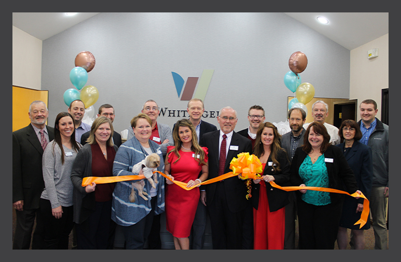 Various Whitinger & Company employees and member-owners, smiling and holding a large yellow ribbon tied in a bow.